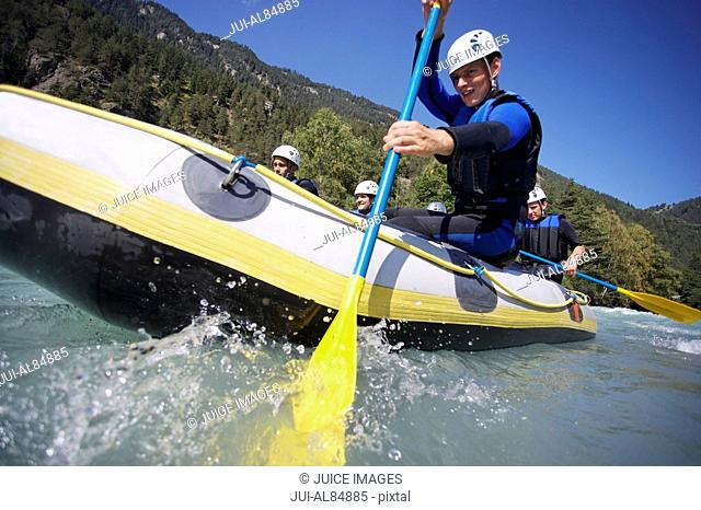 Low angle view of man paddling in whitewater raft