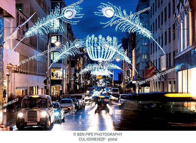 Christmas lights and traffic on city street at dusk, London, UK