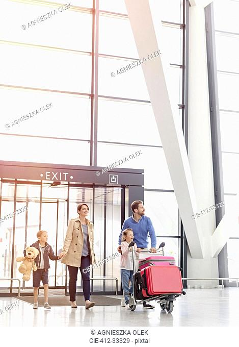 Family arriving pushing luggage cart in airport concourse