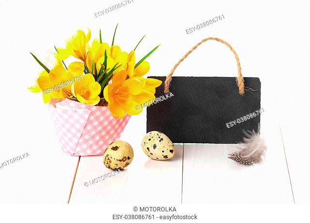 easter decoration with quail eggs, yellow Spring Crocus, and blackboard, with space for text, on wooden white background