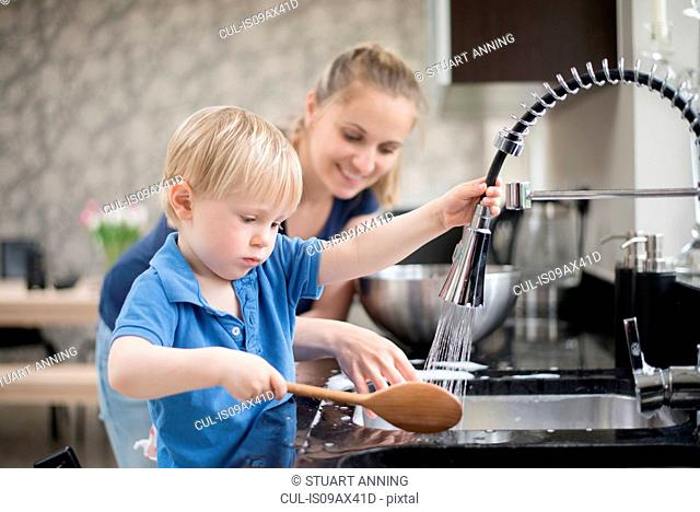 Mother helping son wash wooden spoon