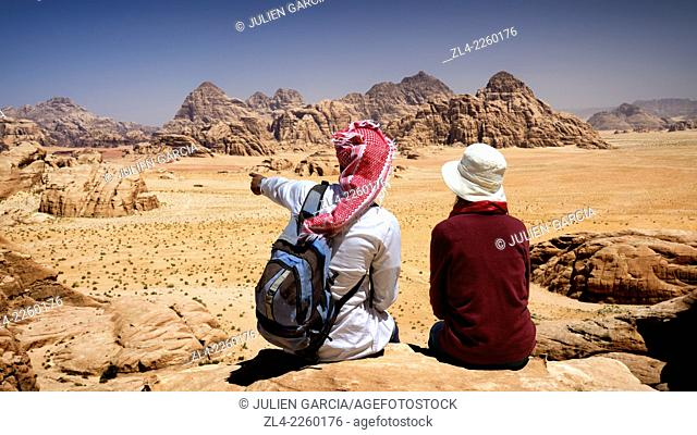 Tourist and local Bedouin guide seated on a rock, contemplating the landscape from the mount Jebel Burdah. Jordan, Wadi Rum desert
