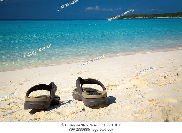 Flip flops on a sandy beach with turqoise water beyond, Halfmoon Cay, Bahamas
