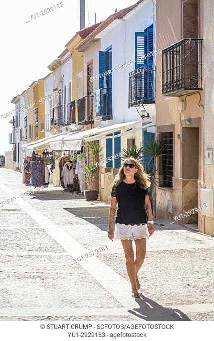 Solo femail tourist walks down the main street of the Spanish island of Tabarca