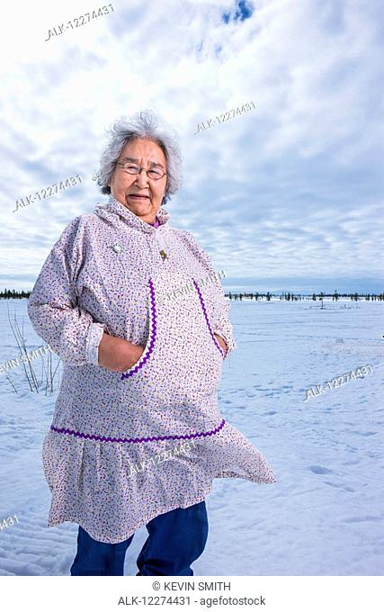 Elder Alaska native woman wearing a Kuspuk parka stands on snow covered tundra, Winter, Noatak, Arctic Alaska, USA