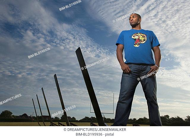 Serious African American man standing on football field