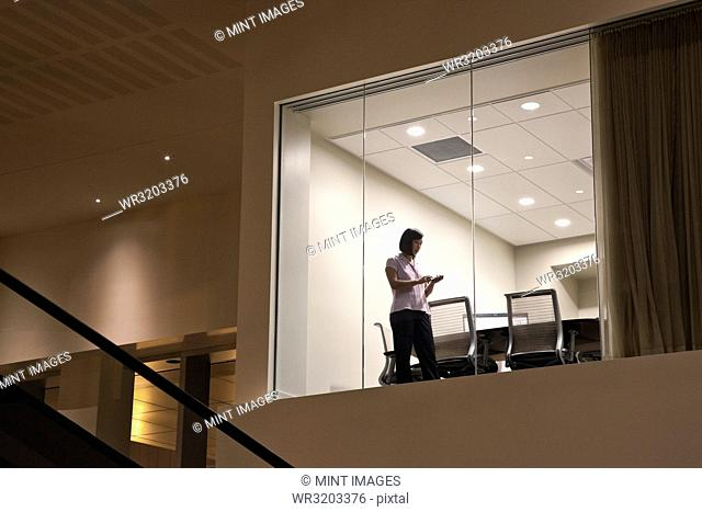A view looking into a conference room at night with two business people at work at a conference table
