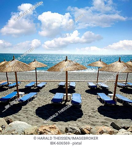Empty beach near by Kokkino Nero with deck chairs and parasols covered with leaves of palm trees Thessaly Greece