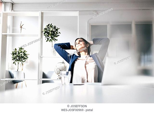Businesswoman at table leaning back