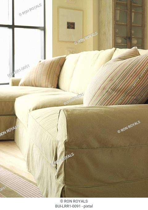 Light colored sofa with striped throw pillow