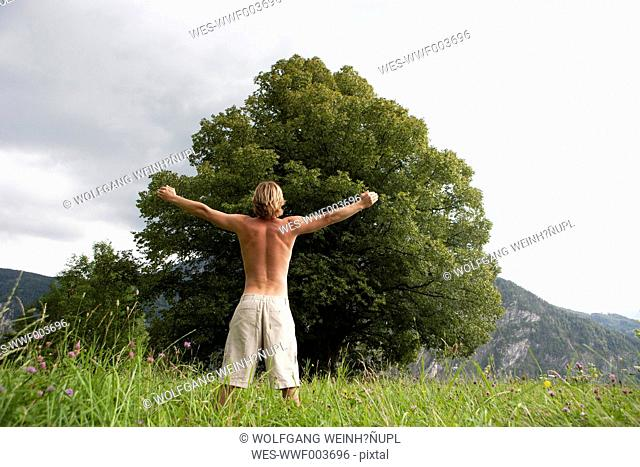 Austria, Salzkammergut, Mondsee, man with outstretched arm standing in front of an old tree