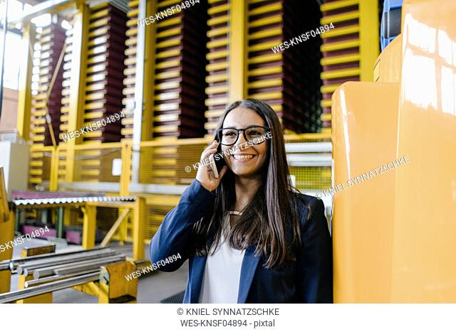 Young woman working in distribution warehouse, talking on the phone