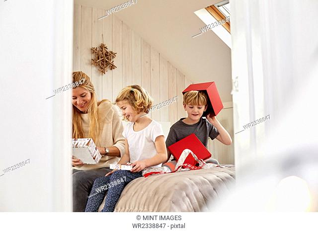 Christmas morning in a family home. A mother and two children sitting on a bed opening presents