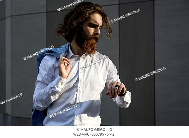Stylish businessman checking the time