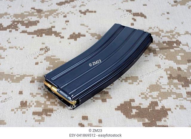 US MARINES M-16 rifle magazine with cartridges on camouflage uniform background