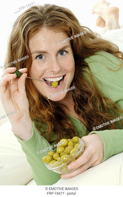 Redhead young woman eating green olives