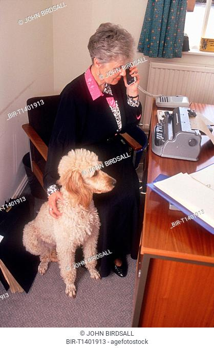 Woman with visual impairment sitting at desk in front of Braille typewriter stroking guide dog and talking on telephone