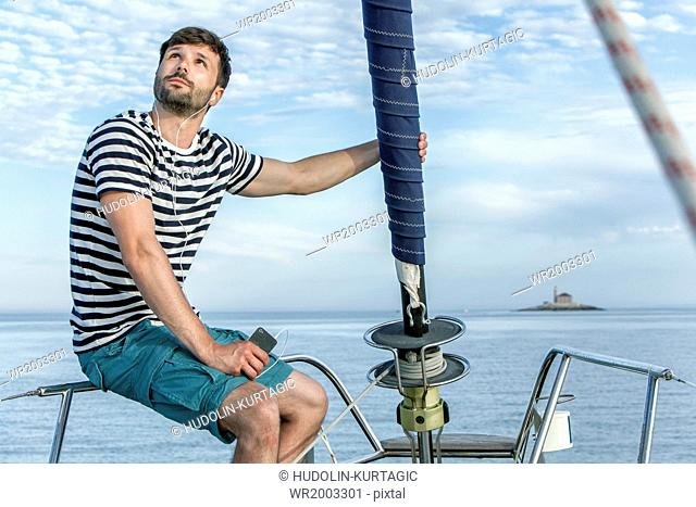 Man listening to music on sailboat, Adriatic Sea