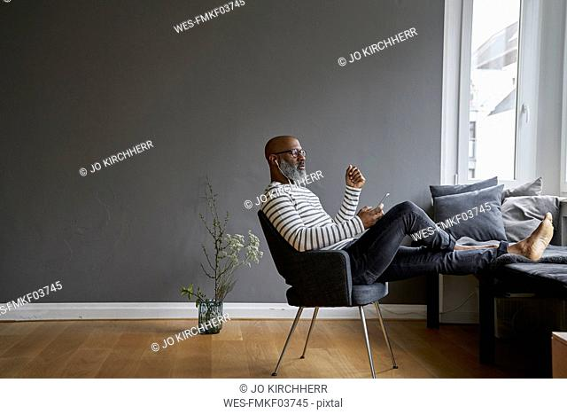 Mature man sitting with feet up, using smartphone