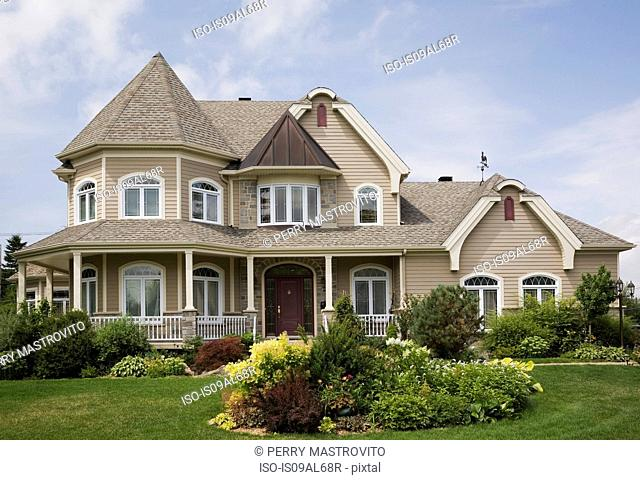 Beige with white trim cottage style house facade, Quebec, Canada
