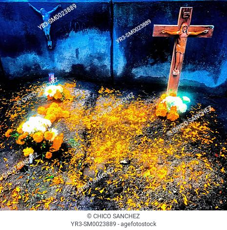 Crosses and marigold flowers decorate a tomb during Day of the Dead celebrations in Mexico City, Mexico