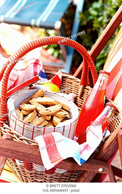 Cantucci biscuits in biscuit tin with glass bottles of juice in picnic basket
