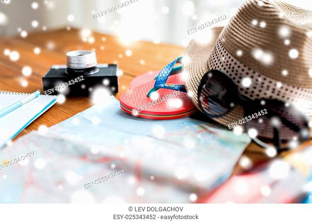 vacation, tourism and objects concept - close up of travel map, flip-flops, hat and camera on wooden table at home