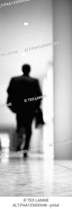 Businessman running in hallway, b&w, vertical, blurred
