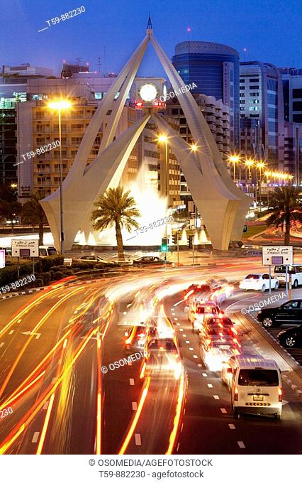Clocktower Roundabout with traffic at Dubai at dusk