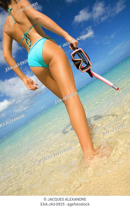Low angle view of woman walking in water with snorkeling gear