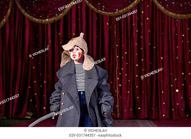 Skilled empathetic boy pretending to be a brave Russian soldier while performing a dramatic act, on stage, against dark red classical curtains