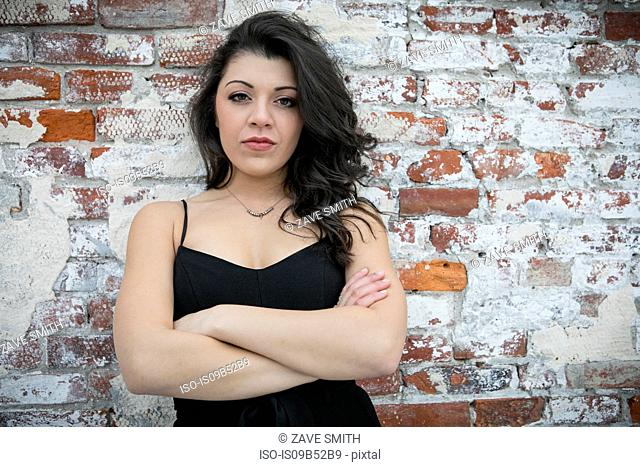 Portrait of confident young woman with arms folded leaning against brick wall