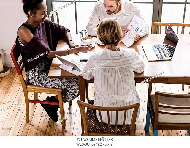 Three young people having a meeting in a cafe