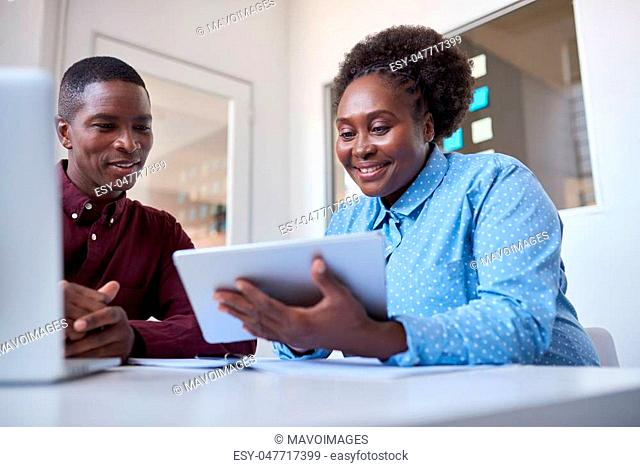 Two casually dressed African colleagues sitting together at a table in a modern office working online with a digital tablet