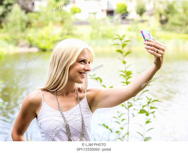 A beautiful young woman taking a self-portrait while enjoying her alone time in a park with a manmade lake; Edmonton, Alberta, Canada