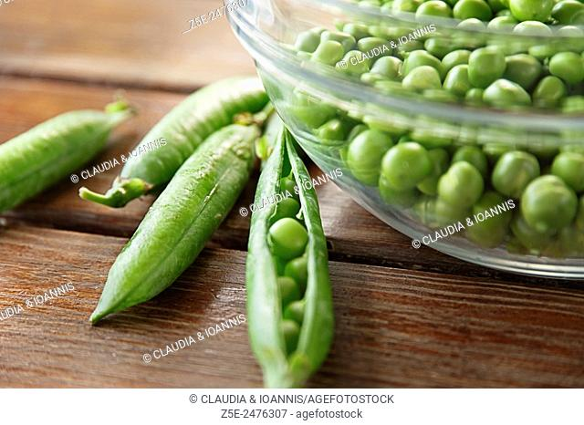 Peapods and glass bowl full of peas