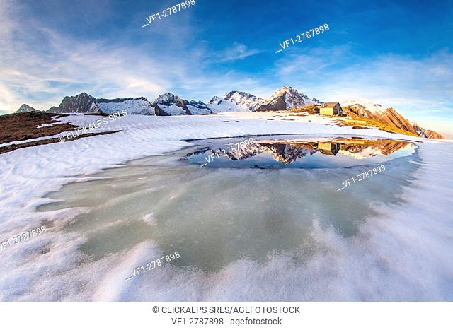 Lake Scermendone during the vernal thaw reflecting Mount Disgrazia at sunset Valtellina, Sondrio, Lombardy, Italy. Europe