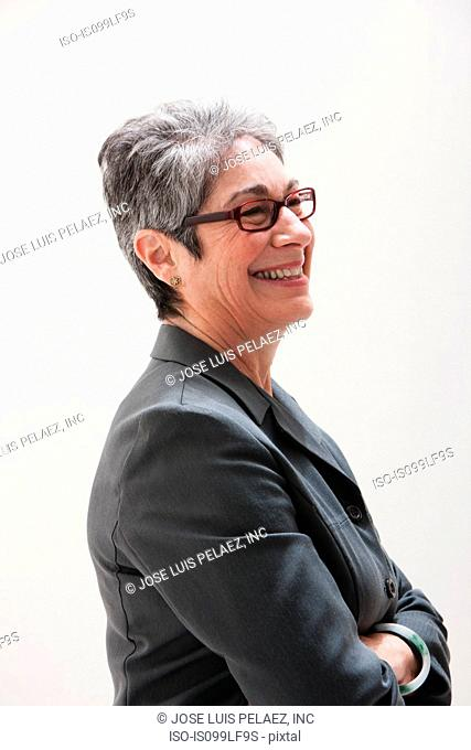Mature businesswoman smiling, studio shot
