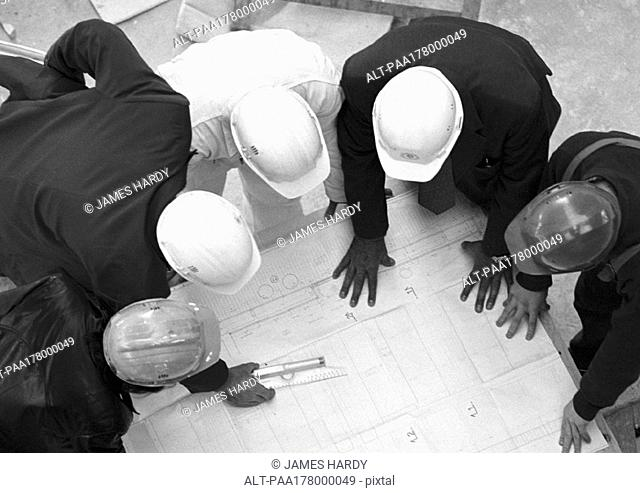 Five people with hard hats, examining blueprints, elevated view, b&w