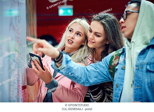 Three young adult friends pointing at map in underground station