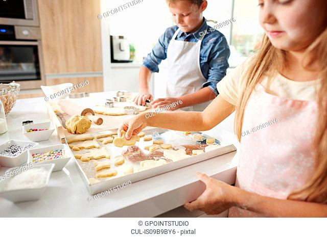 Girl and brother baking easter biscuits at kitchen counter
