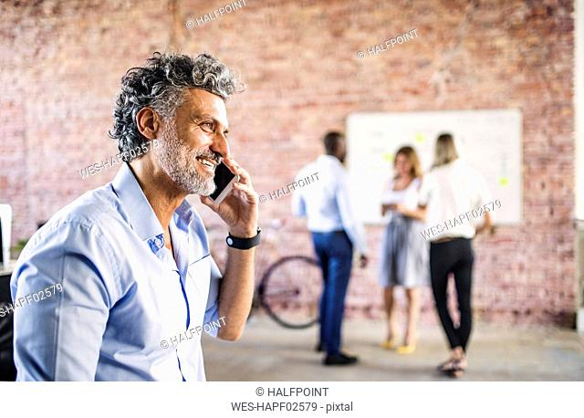 Smiling businessman on cell phone in office with colleagues in background