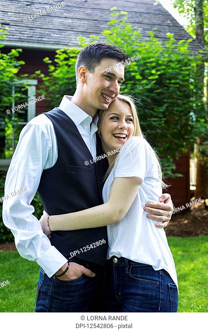 Portrait of a young couple standing in a backyard; Bothell, Washington, United States of America
