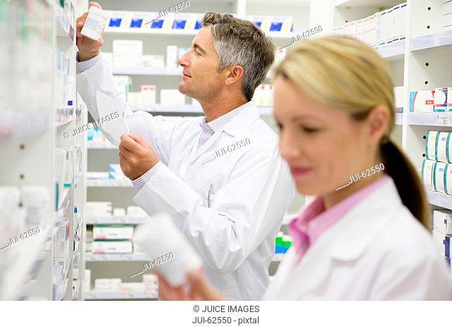Pharmacist searching for bottle of medication on pharmacy shelves