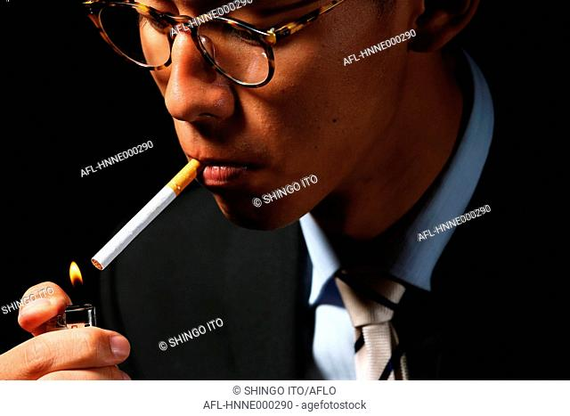 Young Japanese businessman smoking cigarette