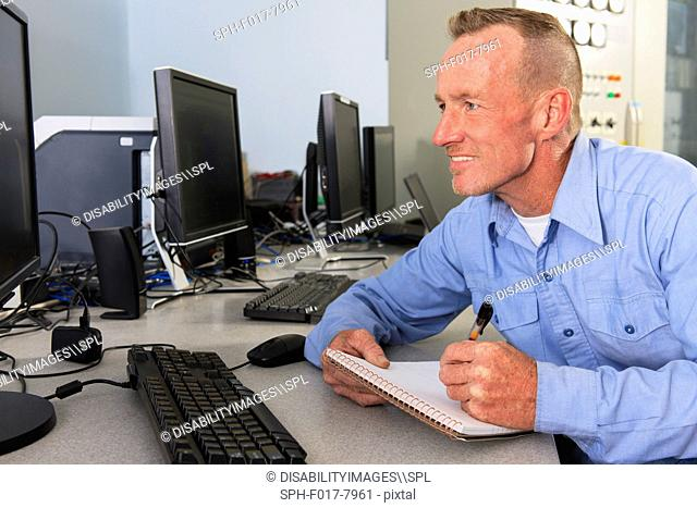 Engineer at electric power plant control room recording a log at management displays