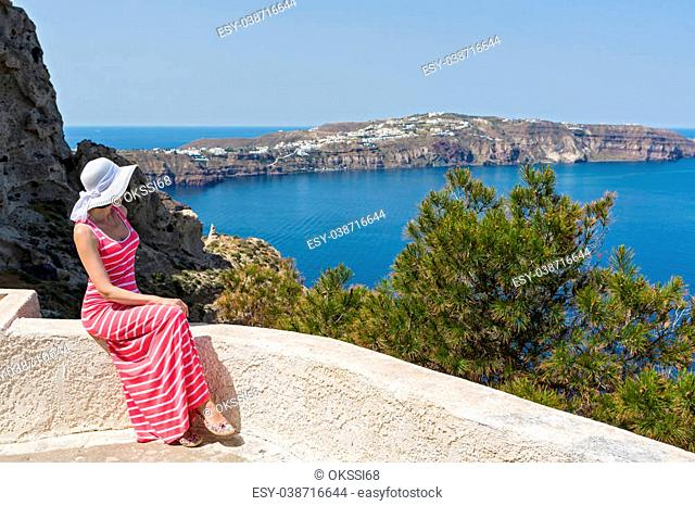 Woman n a long summer dress sits and watches the sea. Greece Santorini