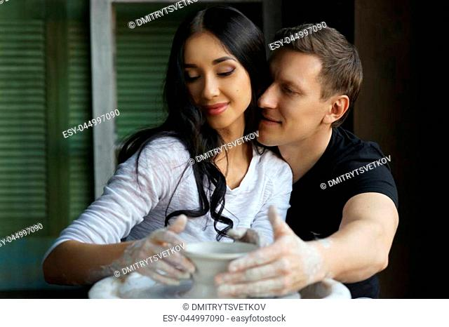 Romantic caucasian couple working on potter whel. Handsome man and pretty beautiful brunette woman making and sculpting clay pot together and hugging