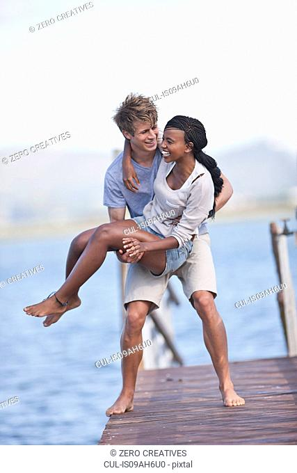 Young couple of jetty, man lifting woman
