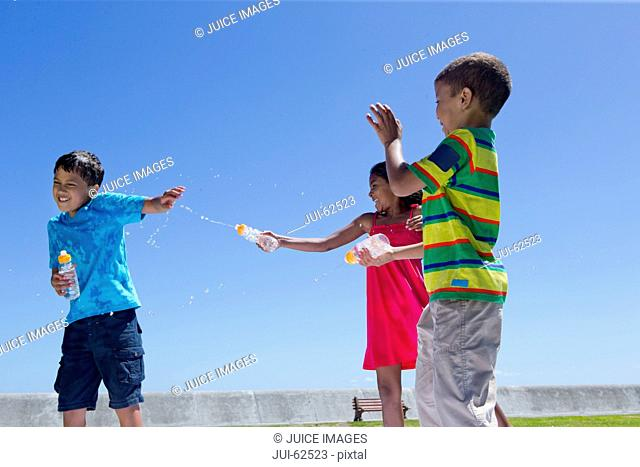 Smiling children having water fight in park